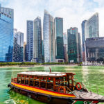 A bumboat docks at the Marina Bay with skyscrapers in the Singapore business district in the background. HDR rendering.